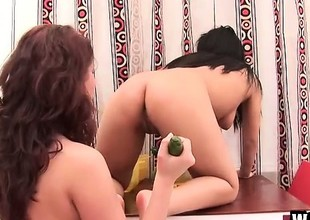 Horny Oriental bitch with bald pussy and her dark brown friend have fun with cucumber