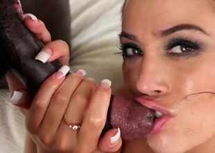 A slut with a sexy face handles a large black cock with her mouth