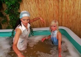 Hawt lesbian honeys get in their soapy pool to romance with their cloths on