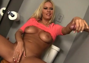 Short haired whorable golden-haired Riley Evans gives oral stimulation through glory hole