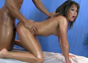 A dark brown with a sexy face is getting massaged by her horny masseur