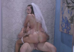 A sexy bride to be is getting fucked on the carpet by a stud