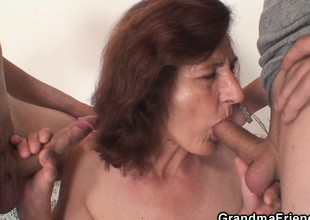 Skinny granny swallows two cocks