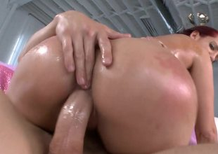 Redhead has plenty of oil on her body to make her more slippery
