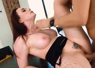 A brunette with large tits is riding a hard pecker like a pro in the office