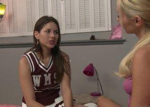 Cute cheerleader and her girlfriend fucking in bed