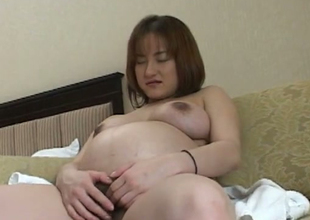 Preggo Japanese woman pleasing her coochie with sex toy