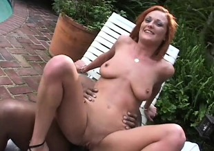 Slutty redhead has a huge black prick drilling her peach by the pool