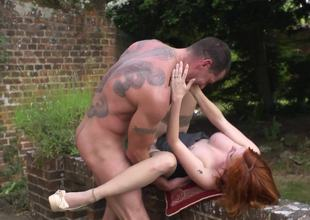 Redhead is outside, in the garden, receiving a large dick in her