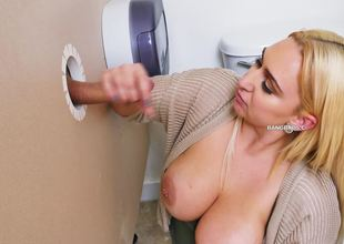 A blonde is taking care of a knob through a glory hole