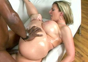 A hot milf with large tits is getting a large black dick in her mouth