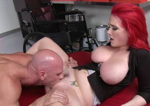 A redhead with huge meatballs is getting tit fucked on the couch